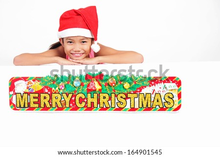 Young happy girl leaning on a white board with christmas sign. - stock photo