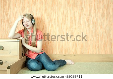 Young   happy girl listening music in headphones on couch - stock photo