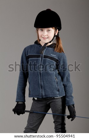 young happy girl.  little girl on a gray background. Young rider. - stock photo