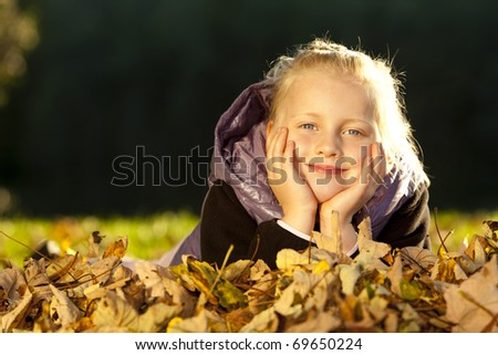 Young happy girl lying on floor in autumn leaves. - stock photo