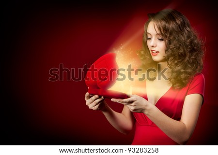 Young happy girl opening a gift on Valentine's Day