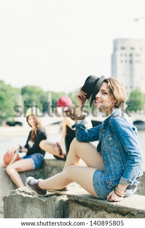 Young happy girl posing in jeans jacket with hat. Outdoors, lifestyle - stock photo