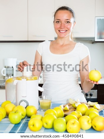 Young happy girl preparing fresh apple juice in domestic kitchen