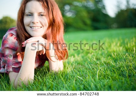 Young happy girl relaxing on green grass.