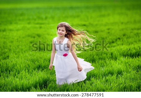 Young happy girl running at green wheat field - stock photo