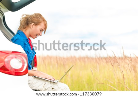 Young happy girl sitting and working on computer. Beautiful woman near car in meadow holding laptop. Person working outdoor. Tail light of car in foreground and field with sky in background. - stock photo
