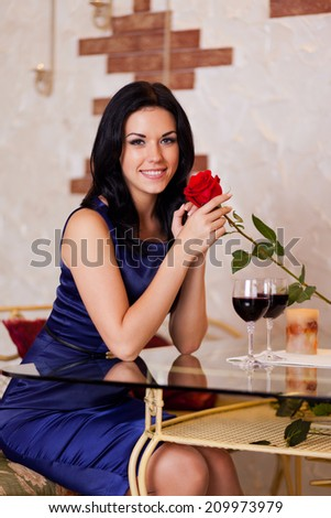 Young happy girl smile with red rose gift, romantic date at restaurant, celebrating valentine day - stock photo