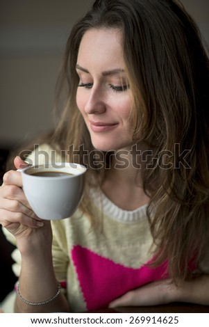 Young happy girl smiling and holding a cup of hot coffee or tea sits in a cafe, lifestyle, breakfast or dinner to spend time relaxing, healthy lifestyle, fashion, in a yellow sweater. - stock photo