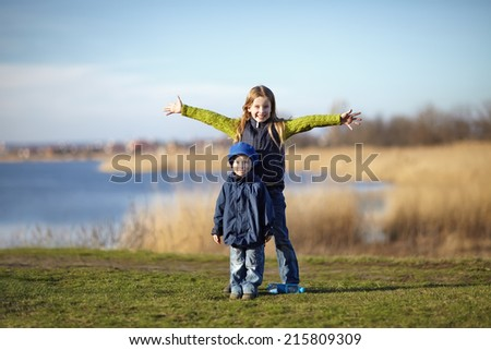 Young happy girl spreading hands with younger brother beside the river. Happy lifestyle kids - stock photo