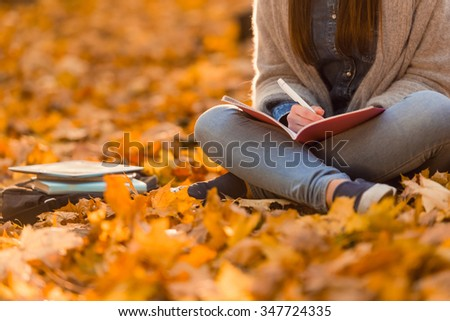 Young happy girl students while walking autumn park - stock photo