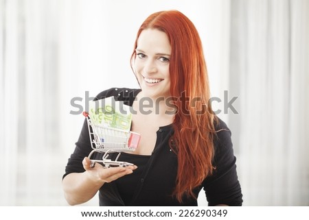 young happy girl with mini shopping cart trolley with euro bank note smiling