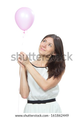 Young happy girl with pink balloon as a present for birthday party smiling and looking at the corner on a white background - stock photo
