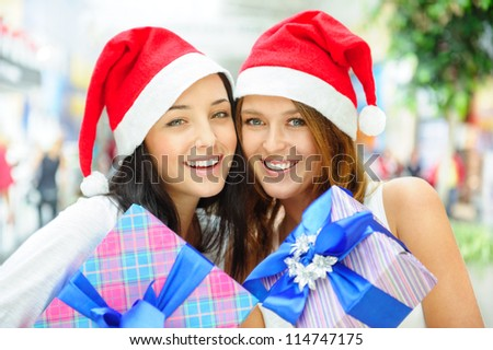 Young happy girls in Christmas hats.Standing together indoors and holding gift boxes