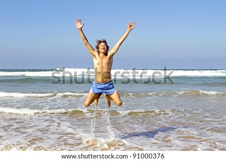 Young happy guy jumping out of the water at the atlantic ocean in Portugal - stock photo