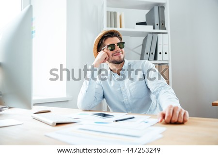 Young happy handsome man sitting at the table in the office