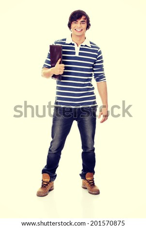 Young happy handsome student man with notebook - stock photo