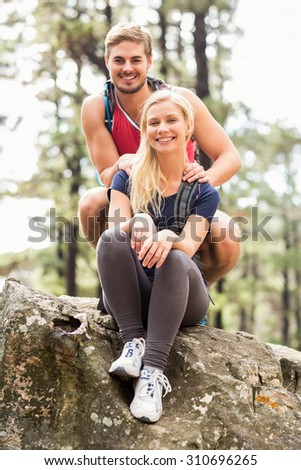 Young happy hiker couple looking at camera in the nature
