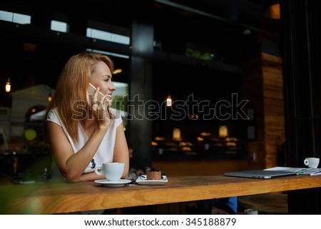Young happy hipster girl speaking with her friend by mobile phone while relaxing in cozy coffee shop, charming lady with beautiful smile talking on cell telephone while sitting in cafe during lunch  - stock photo