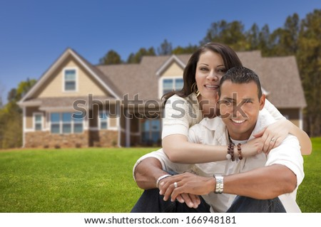 Young Happy Hispanic Young Couple in Front of Their New Home. - stock photo
