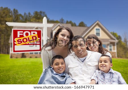 Young Happy Hispanic Young Family in Front of Their New Home and Sold For Sale Real Estate Sign.