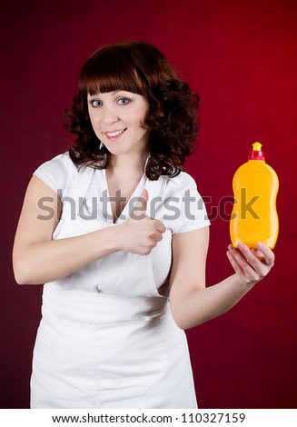 Young happy housewife cleaning dishes - stock photo