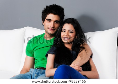 young happy indian couple relaxing on the sofa, happy multi ethnic couple relaxing on white sofa - stock photo