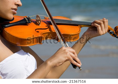 young happy indian violin player play on beach - stock photo
