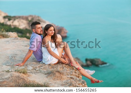 Young happy interracial couple sitting on a mountain near the ocean - stock photo