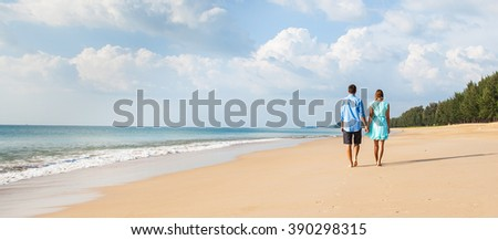 Young happy interracial couple walking on beach .  Banner. Back view. - stock photo