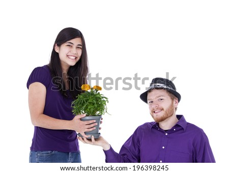 Young happy  interracial couple with potted marigold plant, studio shot - stock photo