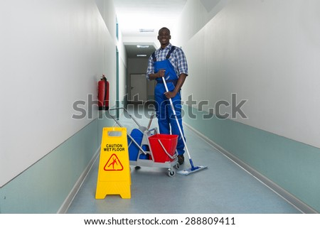 Young Happy Janitor Holding Mop With Bucket And Wet Floor Sign In Corridor - stock photo
