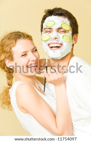 Young happy joyful couple making facial masque at home