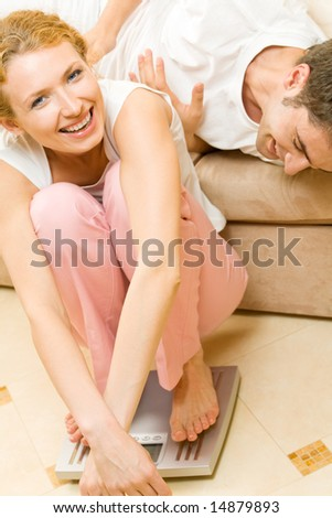 Young happy joyful couple with scales at home - stock photo