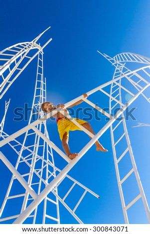 young happy kid - boy - climbing white ladders going nowhere up on natural sky background, outdoor - stock photo