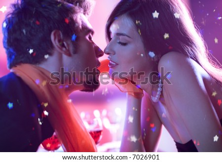 Young happy kissing amorous couple at celebration