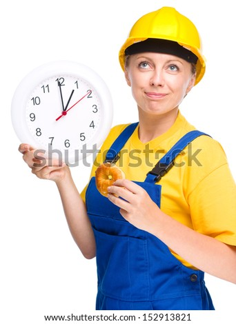 Young happy lady as a construction worker is biting donut while holding big clock, lunchtime concept, isolated over white - stock photo