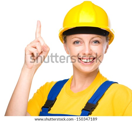 Young happy lady as a construction worker is pointing up with her forefinger, isolated over white - stock photo