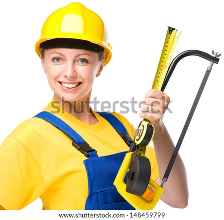 Young happy lady as a construction worker with hacksaw and tape measure, isolated over white - stock photo