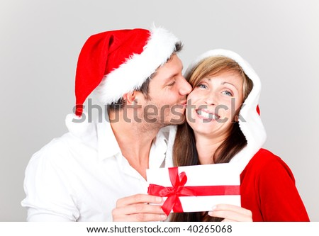 Young happy lovely kissing couple with bonus greeting card wishing a merry christmas
