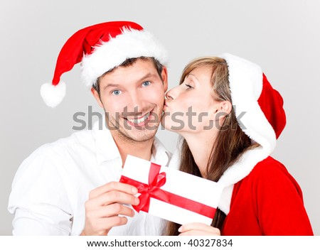 Young happy lovely kissing couple with bonus greeting card wishing a merry christmas - stock photo