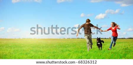 Young happy lovers running with a dog on meadow with green grass and blue sky - stock photo