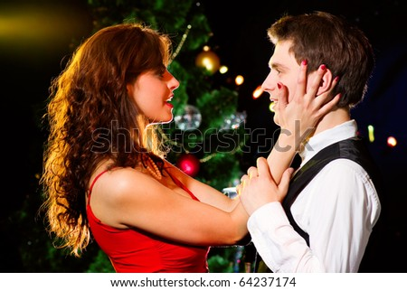 Young happy loving couple dancing at Christmas celebration near New Year's tree, looking to each other - stock photo