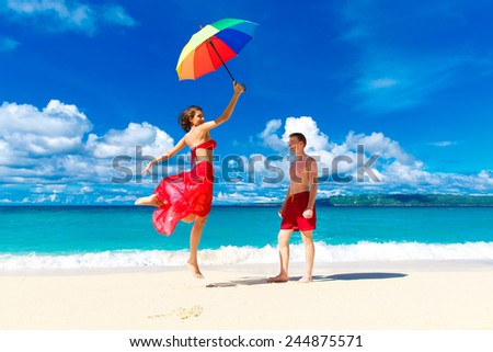 young happy loving couple having fun in the tropical beach with multicolored umbrella