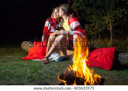 Young happy loving couple sitting on log near the fire covered with plaid holding wine, drinking and enjoy their romantic night. he is kissing her and smiling.  - stock photo