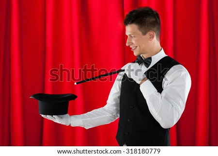 Young Happy Magician With Magic Wand And Black Hat - stock photo