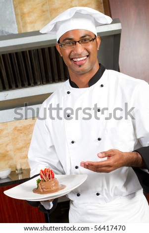 young happy male chef present dessert in commercial kitchen - stock photo