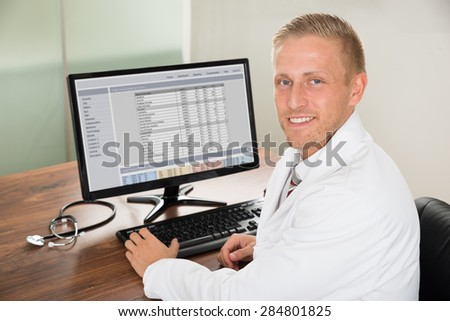 Young Happy Male Doctor Working On Computer At Desk