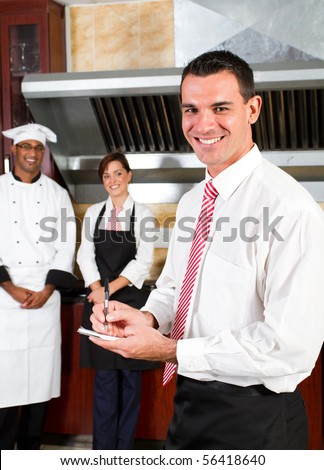 young happy male restaurant manager and his staff in kitchen - stock photo