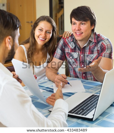 Young happy male try hard to sign a contract with merried couple
