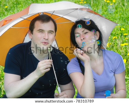 Young happy man and smiling woman blowing soap bubbles